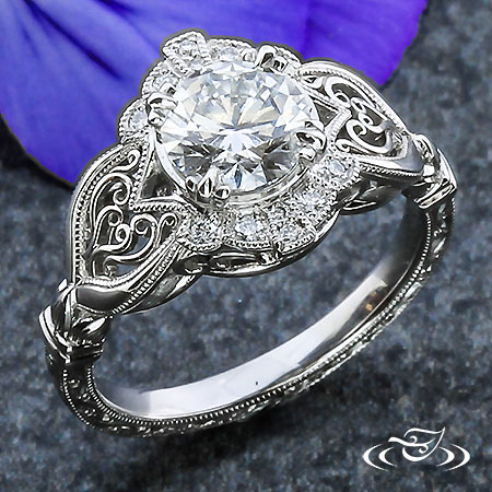 PLATINUM AND DIAMOND ENGAGEMENT RING WITH HEART-SHAPED FILIGREE ACCENTS
